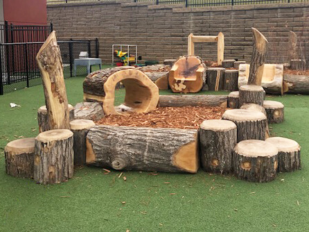 picture of an early outclass outdoor learning pod with log border wacky posts and log tunnel