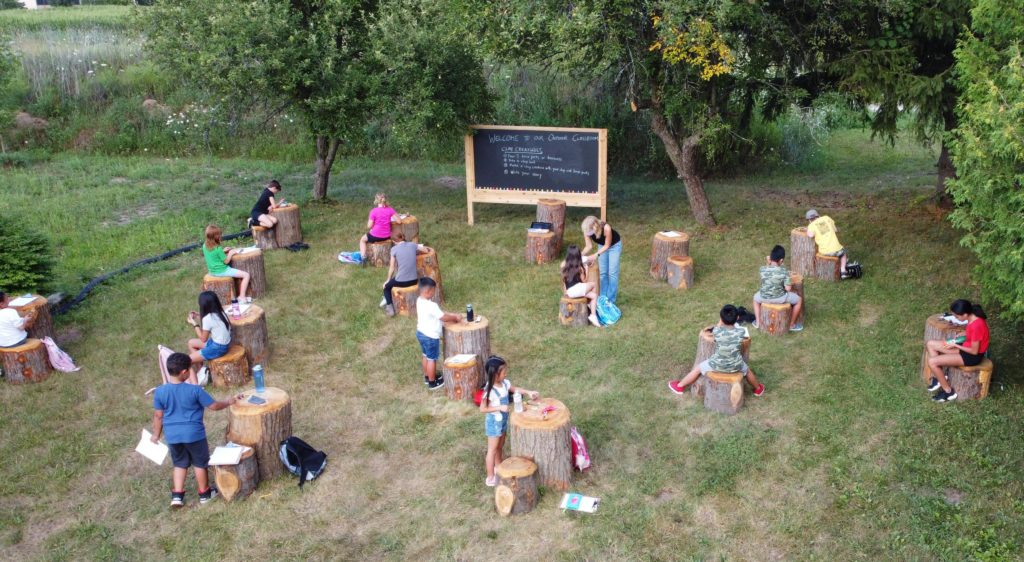 picture of children sitting in an outdoor classroom